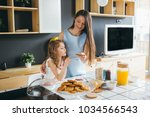 mother and daughter making... | Shutterstock . vector #1034566543
