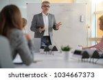 teacher giving economics class  ... | Shutterstock . vector #1034667373