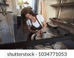 female artisan sitting at a... | Shutterstock . vector #1034771053
