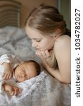 blonde little girl and 1 month... | Shutterstock . vector #1034782027