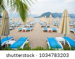 sun loungers on a beach in... | Shutterstock . vector #1034783203