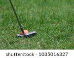 orange golf ball and putter on... | Shutterstock . vector #1035016327