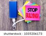 Small photo of Stop Bullying. Business concept for Prevention Problem Bully written on sticky note with space on old wood wooden background with power bank