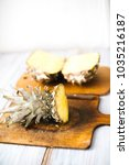 Small photo of Ripe bisected ripe pineapple on a wooden background