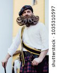 Small photo of Portrait of a brave Scot with a amazing beard and mustache curls in the Hungarian style. Checkered red Scottish kilt skirt, hat with pompon, cane and sword. Beard styling by professional barbershop.