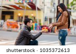 young man giving a gift as to a ... | Shutterstock . vector #1035372613
