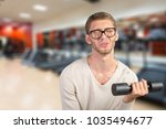 funny weak man tries to lift a... | Shutterstock . vector #1035494677