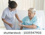 Small photo of caregiver nurse helping elderly woman taking medicine on the bed and check up after admit inpatient in hospital.