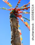 Naxi tribe totem pole attached with colorful Tibetan prayer flags in Dongba Valley, Lijiang, Yunnan Province of China. - stock photo