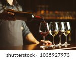 bartender pours red wine in... | Shutterstock . vector #1035927973