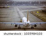 Small photo of airplane at parking apron view from window of waiting hall of air terminal in late afternoon on a cloudy day