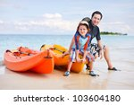 Happy father and son after kayaking relaxing near boats - stock photo