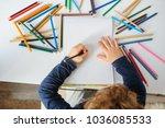 top view of little boy paints... | Shutterstock . vector #1036085533