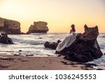 a lonely girl sits on the rocks ... | Shutterstock . vector #1036245553