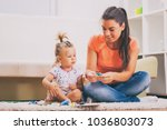 mother and daughter in their... | Shutterstock . vector #1036803073