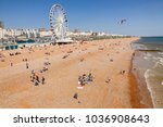 Small photo of BRIGHTON, UK - JUN 5, 2013:View along the Brighton Beachfront with the Ferris Wheel promenade and vacationer on shingle beach pictured from the Brighton Palace Pier on a sunny summer day