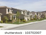 Suburban homes run upwards along a hill side. - stock photo