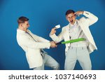Small photo of Businessman batting rival with baseball bat. Man showing finger gun with blank card. Managers shouting and fighting on blue background. By force or persuasion. Business negotiations concept.