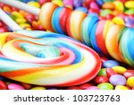 Striped lollipops and multicolored smarties - stock photo