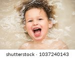 a young child is soaking his... | Shutterstock . vector #1037240143