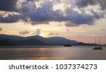 sunset at sea  mountains in... | Shutterstock . vector #1037374273