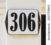 enameled house number three hundred and six. Black lettering on a white plate. - stock photo