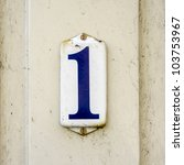 enameled house number one. Blue lettering on a white background - stock photo