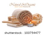 Rolled towel with natural bath, spa, sauna and body care toiletries - stock photo