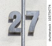 metal house number twenty-seven, divided by a vertical pipe. - stock photo