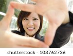 Smiling Asian business woman making a frame with fingers - stock photo