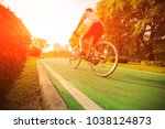 a woman is cycling into the... | Shutterstock . vector #1038124873