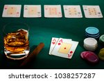 Small photo of Texas hold'em poker with a hand of two aces, chips, cigar, and glass of whiskey on green broadcloth. Won by three aces.