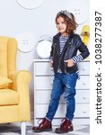 Small photo of Fashion style clothes for child small little girl wear strip t-shirt denim jeans lather jacket boots hat bow cute pretty face curly hair baby model fun play room color furniture yellow chair toy game.