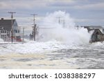 Small photo of Wells, Maine, USA: February 3, 2018: A storm wave crashes over two telephone poles and the roof of a beach front house in wells Maine during high tide causing massive flooding.