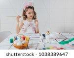 little girl painting easter eggs | Shutterstock . vector #1038389647