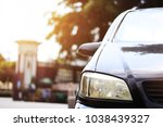 Small photo of Close up and Focusing on the old right headlight of black car parking on a street corner in the daytime. With the sunlight and blur view building background
