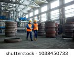Small photo of Bearded young worker wearing reflective vest and hardhat showing results of accomplished work to his superior while walking along production department of modern plant