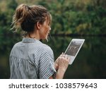 woman alone in nature using a... | Shutterstock . vector #1038579643