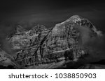 Small photo of Peaks Tofana di Rozes and Tre Dita with gentle snow girded by clouds in black and white with exceptional light atmosphere