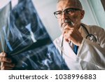 mature doctor examining the... | Shutterstock . vector #1038996883