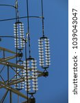 Small photo of Glass Insulators High Voltage connected on electricity tower on bleu sky as background