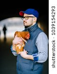 Small photo of Strange unusual bald beardy man with serious senseless face in glasses standing in dark city tunnel. Oddball boy with chiken in hands. Adult male with lovely pet. Happy friends. Weird love. Birdman