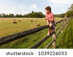 boy sitting on the fence with a ... | Shutterstock . vector #1039226053