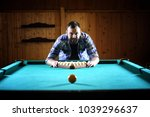 Small photo of A man with a beard plays a big billiard. Party in 12-foot pool. Billiards in the club game for men. A man with a cue breaks the pyramid.