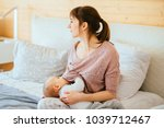 one year old baby eating mother'... | Shutterstock . vector #1039712467