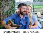 Small photo of Girl with happy face fall in love with bearded man, couple reads poems. Romantic couple holds old books with poems. Romantic date concept. Couple in love sit in cafe outdoor, nature background.