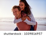 man giving woman piggyback on... | Shutterstock . vector #1039816957