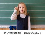 Small photo of First grade pupil a girl writing on green blackboard at school lesson