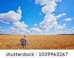 farmer walking through a golden ...   Shutterstock . vector #1039963267