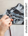 Small photo of Caucasian female hands holding airbrush and drawing picture of mountains, close up view